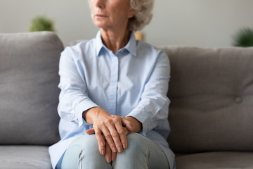 Thoughtful older woman sitting on couch, thinking about life
