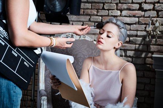 Makeup artist working on diva before shooting