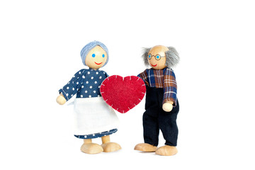 Dolls Elderly man and woman. Grandfather gives grandmother a heart a symbol of love and trust. Valentine's day, love. On white background.
