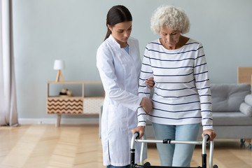Serious doctor teaching disabled older woman to use walker
