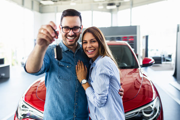 Beautiful young smiling couple holding a key of their new car.