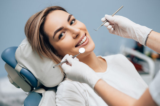 portrait of young smiling blond good-looking woman on dental examination, treating teeth in professional orthodontic clinic