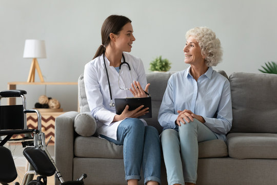 Friendly doctor consulting disabled woman, giving prescription at home