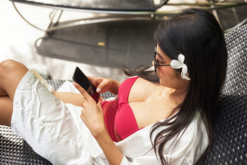 Sexy woman play smartphone at swimming pool