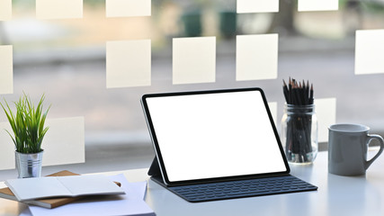 Blank screen computer tablet in a leather-case and keyboard is setting on a modern working table over comfortable office background.