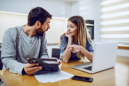 Young attractive bearded man holding electricity bill and showing to his girlfriend how much they spent. Woman pointing at bill and wondering.