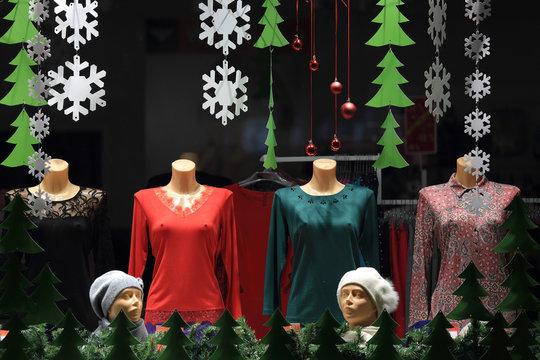 Sukienki na manekinach w witrynie sklepu.