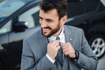 Handsome smiling Caucasian bearded businessman in suit fixing his tie. In background is his car.