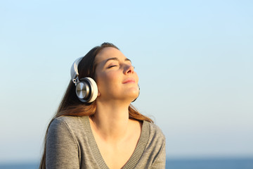 Woman wearing headphones meditating listening to music