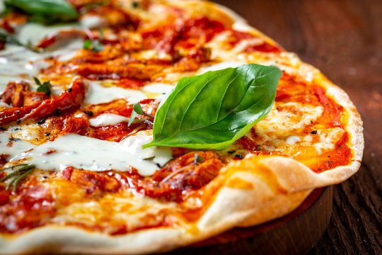 Long pizza Margarita with sun-dried tomatoes and Basil on a wooden Board, close up. Italian cuisine rustic style