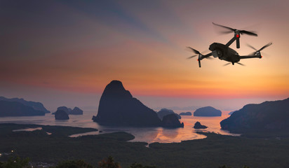 Drone quad copter with high resolution digital camera on the sky mountain and sea side background.