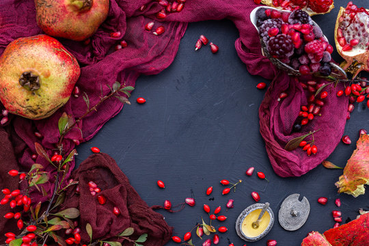 Empty black table with red props and autumn fruits, blank flat lay scene.