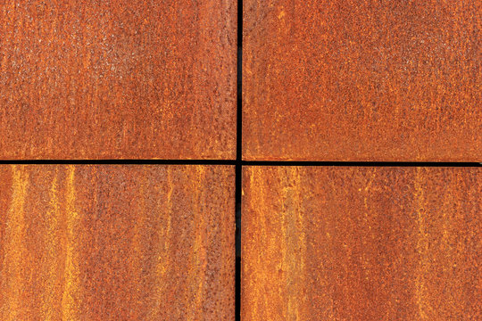 Rusted metal plates with crosswise border lines divided into four equal parts. Iron corroded texture background. Rusty metal surface.