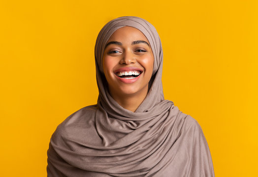Portrait of sincerely laughing black muslim woman over yellow background