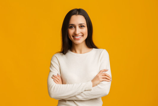 Beautiful brunette woman standing with folded arms over yellow background