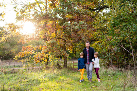 Father walking with his two daughters in a park during autumn