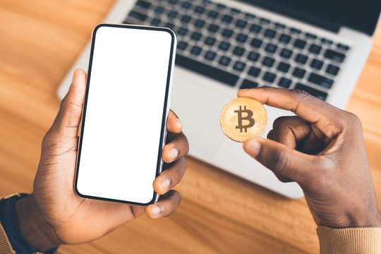 African american guy holding golden bitcoin and phone