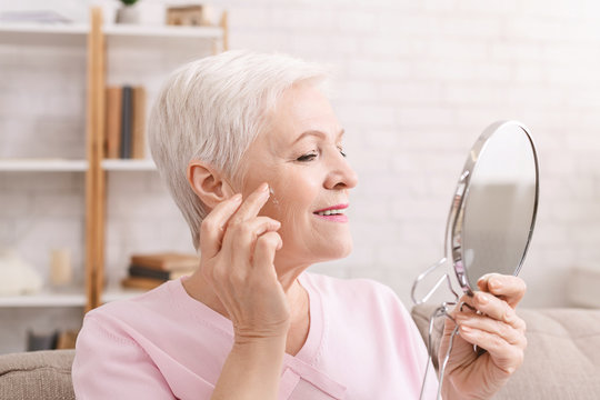 Senior lady applying anti aging cream around wrinkles