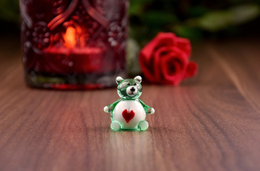 Cute bear with heart stock images. Romantic figurine of teddy bear. Glass teddy bear on a wooden background. Valentines Day concept
