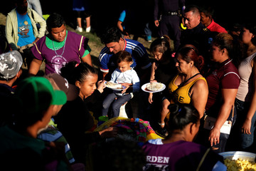 Women and children travelling to the U.S. stand in a line to get breakfast in an improvised shelter in Tecun Uman