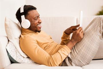 Happy Guy In Headphones Using Tablet Lying On Couch Indoor