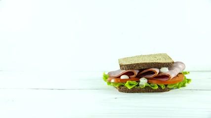 Fototapete - make cooking sandwich, bread, ham, lettuce, sauce, tomato. Time lapse. Close up