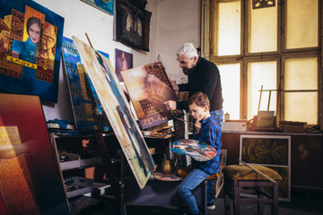 Father and son working and painting together in art studio
