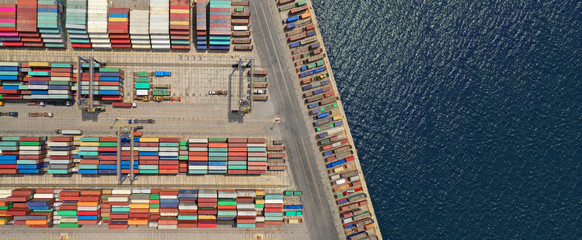 Aerial drone ultra wide top down photo of commercial container terminal with cranes loading shipment to tanker ships in Mediterranean port