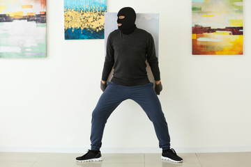 Thief stealing picture from art gallery