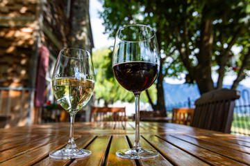 pair of different glass sizes and wines, red and white wine glasses on wooden furniture table close up selective focus, vineyard farmhouse patio view
