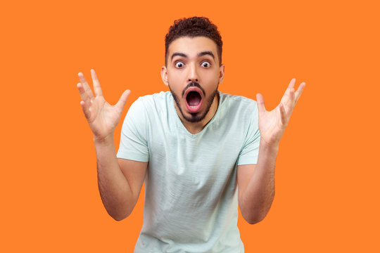Oh my god, wow! Portrait of amazed brunette man with beard in white t-shirt staring at camera with big eyes and open mouth, absolutely shocked by news. indoor studio shot isolated on orange background