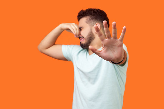 Stinky smell. Side view of confused brunette man with beard in white t-shirt holding breath with fingers on nose, disgusted by bad odor fart, gesturing stop. studio shot isolated on orange background
