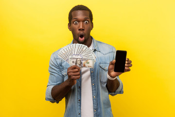 Wow, profitable service, online banking. Portrait of surprised excited man in denim shirt holding dollars and smartphone, making money in mobile application. studio shot isolated on yellow background