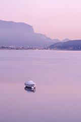 Abbadia Lariana, Lecco, Lombardy, Italy, January 11, 2020 - Boat on the lake Como at pink twilight