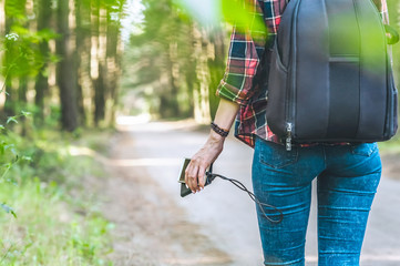 Power bank in the girl s hand, against the background of the forest and the road.