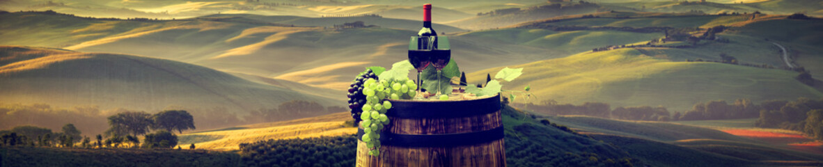 Spoed Foto op Canvas Wijn Red wine bottle and wine glass on wodden barrel. Beautiful Tuscany background