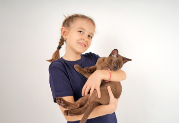 Girl playing with a cat on a white background