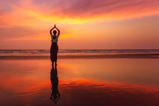 Beautiful yoga meditation reflection on water Goa beach on sunset