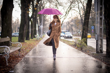 Confident woman walking on the street on a rainy day