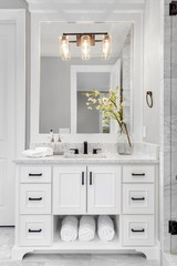 Bathroom in traditional style luxury home with vanity, mirror, sink, and tile floor