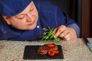 Grilled steak with micro-greens and tomatoes on black square plate. Male chef hand decorating uncooked steaks.