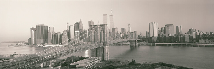 Wall Mural - This is the Brooklyn Bridge over the East River. The Manhattan skyline is behind it at sunrise.