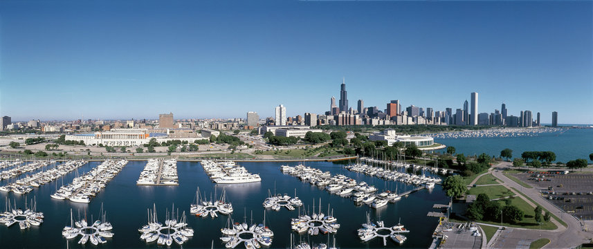 This is an aerial view of the Shedd Aquarium, Chicago Harbor and the skyline on Lake Michigan during summer. Boats are moored in the harbor in the foreground.
