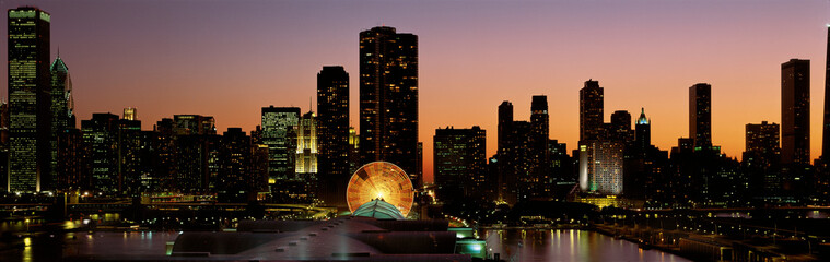 Fototapete - This is Navy Pier and the skyline at sunset during summer. The Ferris wheel on Navy Pier is to the right of center in front of the Lake Point Tower condominium building.