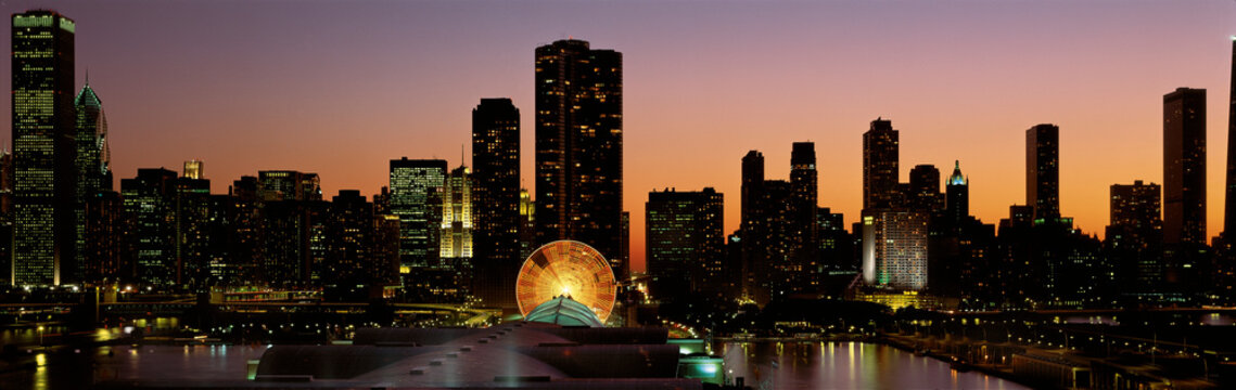 This is Navy Pier and the skyline at sunset during summer. The Ferris wheel on Navy Pier is to the right of center in front of the Lake Point Tower condominium building.