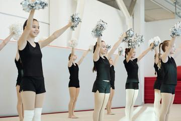 Teenage cheerleaders waving pompons