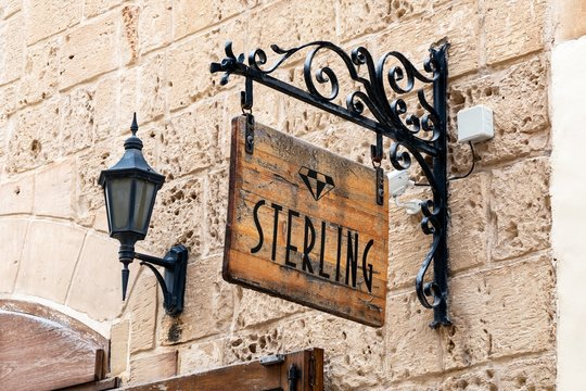 The logo of Maltese Sterling Jewellery which was founded in 1896 on a retro wooden banner