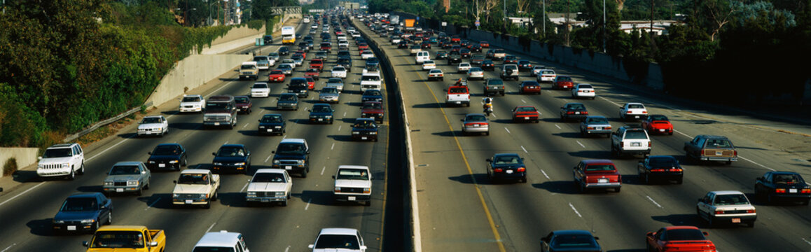 This is rush hour traffic on the 405 Freeway at sunset. There are 10 total lanes of traffic with cars traveling in both directions.