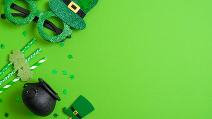 St Patricks day banner design. Top view pots of gold, drinking straws with shamrock four leaf clover, leprechaun hat and Patricks day glasses on green background. Saint Patrick's day greeting card