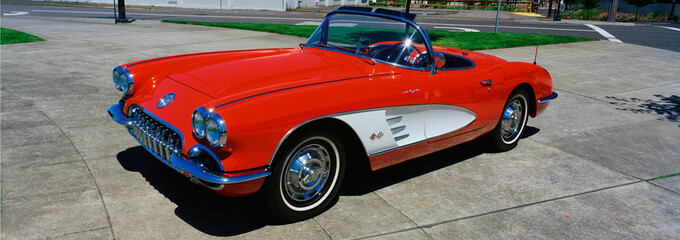 Ingelijste posters Vintage cars This is a restored 1959 Corvette. It is bright red with a white side panel with white sidewall tires. The convertible top is down. It is parked on flat pavement.